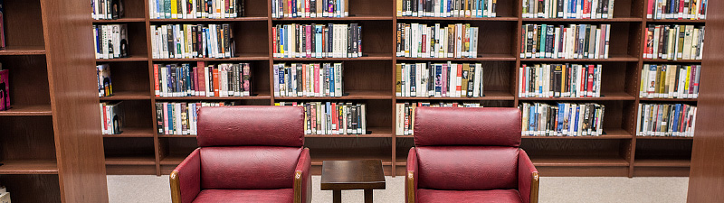 Two crimson leather chairs with a table in between at Bolivar County Library System