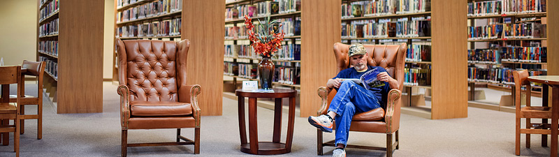 Man reading a newspaper in a large chair at Bolivar County Library System