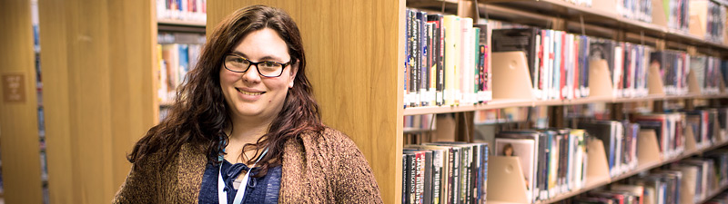Librarian smiling in front of book shelves at Bolivar County Library System