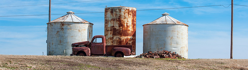 old abandoned truck against grain silos in the Mississippi delta